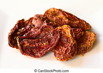 Sun-Dried Tomatoes - Sun-dried tomato halves on white plate,...
