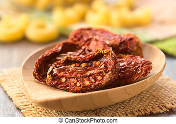 Sun-Dried Tomatoes - Sun-dried tomato halves on bamboo plate...