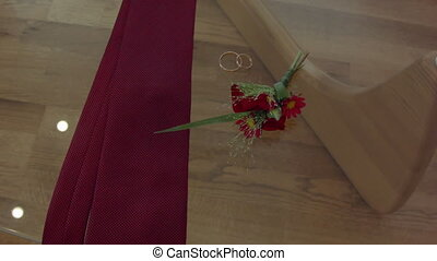 male attributes. tie, rings, flowers lay on a glass...