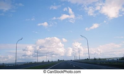 Open road with clouds and blue sky, day highway with lights,...