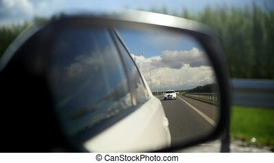 View of the road in the rearview mirror of a car on summer...
