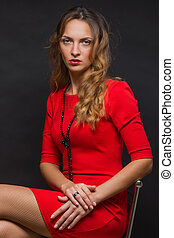 The beautiful young girl in a bright red dress sits on a...
