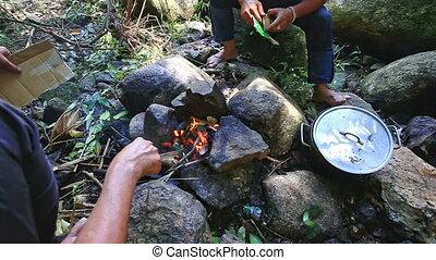 People Cook Food in Pan on Bonfire - closeup people cook...