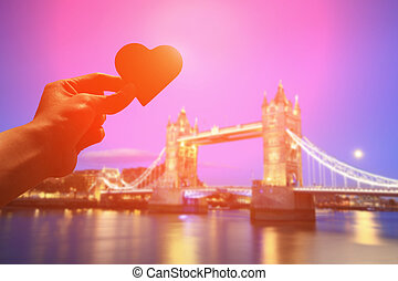 silhouette of romantic lovers hand hold love heart paper in...