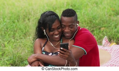 Couple Listening To Music And Watching Video On Mobile Phone...