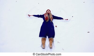 Happy woman making snow angel - Beautiful joyful young woman...
