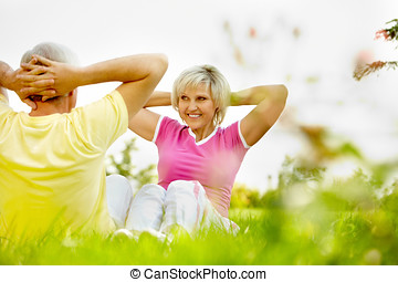 Keeping fit in nature - Senior couple practicing gymnastics...