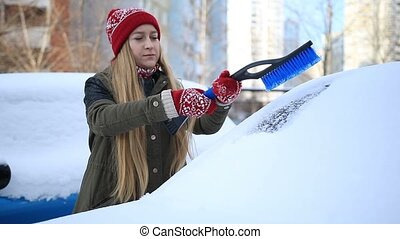 Woman removing snow from car windshield - Young pretty...