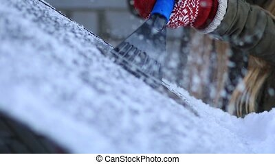 Woman scraping the frost from car windshield - Close up...