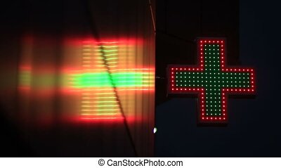 Illuminated green and red pharmacy sign at night