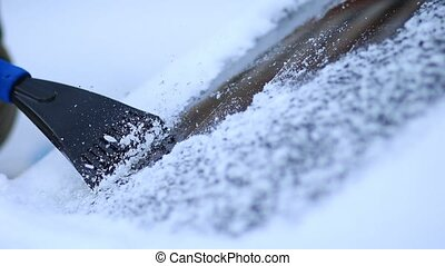 Winter driving - scraping ice from a windshield - Close up...