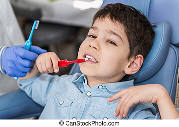 Learning about dental hygiene - Dentist with little boy,...