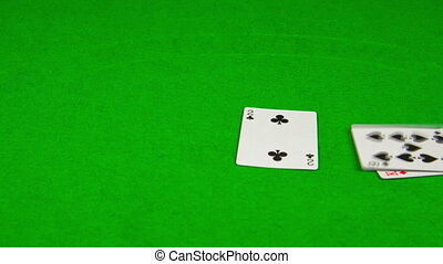 playing cards falling on green table.