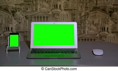 the laptop is on the table,  the smartphone is on the stand, chromakey