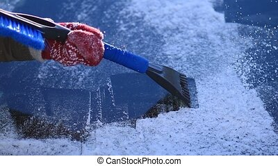 Scraping ice from car's front windshield window - Close up...