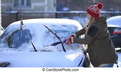 Lady removing snow from windshield with snow brush -...