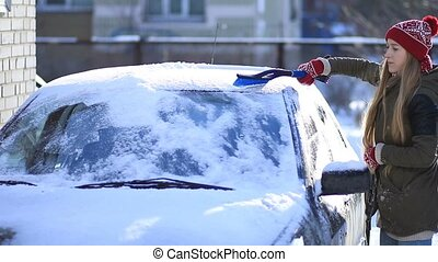 Woman cleaning snow from car roof using brush - Young...