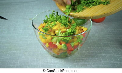 Cook pours in a bowl salad ingredients - The girl cook pours...