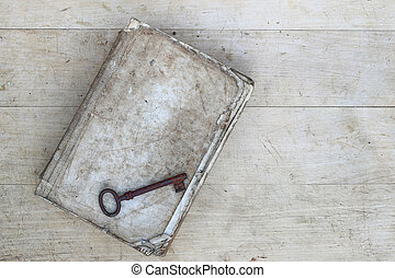Old rusty key on torn book