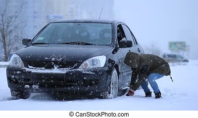 Woman shoveling and removing snow from her car's wheel. The...