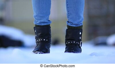 Female feet in black leather winter shoes in snow - Close up...