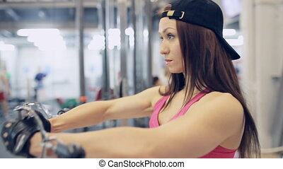 muscular woman doing Cable Crossover Exercise in the gym -...