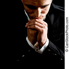 Businessman praying - Low-key portrait of businessman...