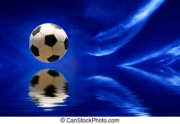 Soccer ball reflecting in water and blue sky as background
