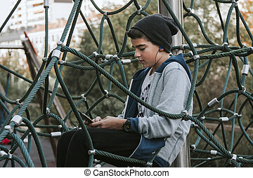 boy in the park listening to music with the phone