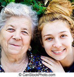 Grandmother with her grand daughter - Closeup portrait of...