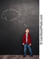 Child thinking with thought bubble over chalkboard