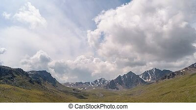 The clouds over the peaks of Kyrgyzstan. Panorama. Time...