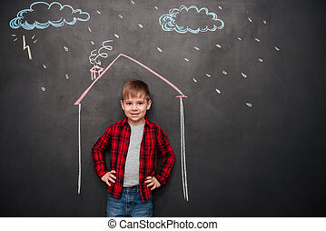 Kid standing in house on chalkboard with drawings of rain