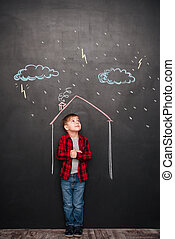 Cute kid standing in house on chalkboard with drawings