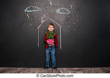 Kid standing in house on chalkboard while holding flower