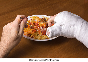 Young man in an arm cast eating pasta - Young man wearing an...