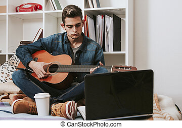 teen in the room playing the guitar