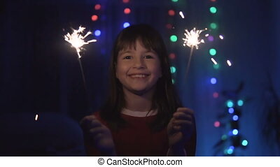 Girl Having Fun with Sparkler - Young smiling happy girl...