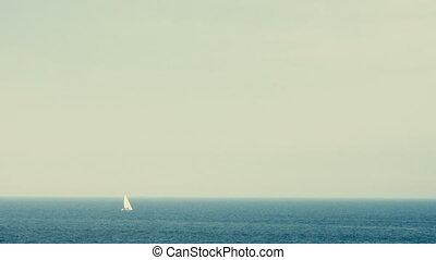 White sail yacht far on the horizon over sea.