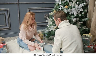 young married couple arranges gifts under the Christmas tree...