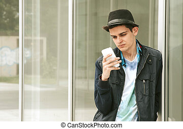 teen male with the cellphone in the city
