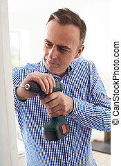 Man Using Electric Drill In House Renovation Project