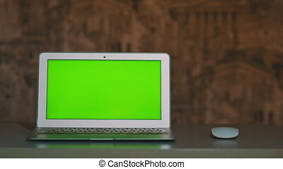 the laptop is on the table, lying next to the mouse the chromakey