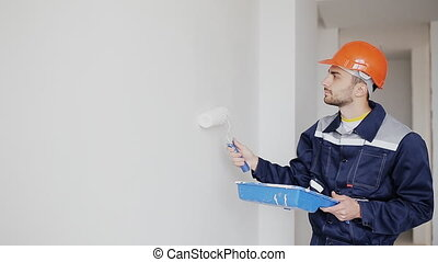painter man at work, with roller painting wall