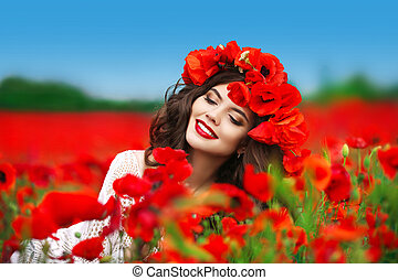 Beautiful happy smiling woman portrait with red flowers on head enjoying in poppies field nature background. Makeup and curly hair style.