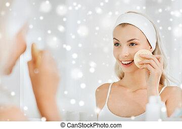 young woman washing face with sponge at bathroom - beauty,...