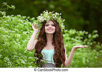 Portrait of smiling young woman in green spring park with open empty palm hand for copy space. Beautiful female with healthy long curly hair posing outdoors.