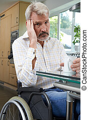 Depressed Man Sitting In Wheelchair At Home