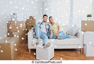 happy couple with big cardboard boxes at new home - moving,...