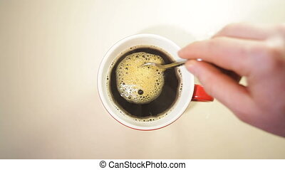 man stirs coffee in a cup on the table.